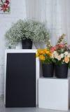 Tre svarta buskets med blommor och det svarta skrivbordet Royaltyfria Foton