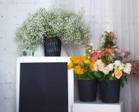 Tre svarta buskets med blommor och det svarta skrivbordet Royaltyfria Bilder
