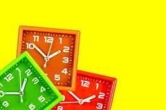 Tre sveglie luminose su un fondo giallo Tavola di orologio verde ed arancia e rosso fotografia stock