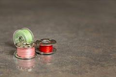 Tre symaskinspolar med gröna rosa färger och den röda tråden Arkivbild