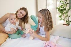 Tre systrar behandla som ett barn flickabarn i morgonen på sängen i sovrummet arkivfoton