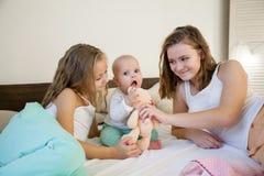 Tre systrar behandla som ett barn flickabarn i morgonen på sängen i sovrummet royaltyfri fotografi