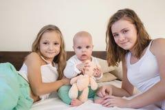 Tre systrar behandla som ett barn flickabarn i morgonen på sängen i sovrummet arkivbilder