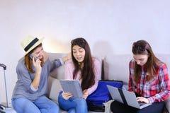 Tre systrar för unga kvinnor använder grejer och meddelar med varje Fotografering för Bildbyråer