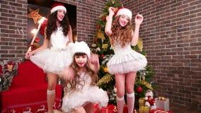 Tre systrar i karneval kostymerar att dansa nära julgranen, den lyckliga familjen som firar helgdagsaftonen för ` s för det nya å stock video