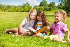Tre systrar läste boken i parkera Royaltyfri Bild