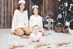 Tre systrar som framme poserar av julgranen Fotografering för Bildbyråer