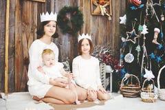 Tre systrar som framme poserar av julgranen Royaltyfri Foto
