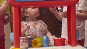 Tre systrar som spelar i leksakkök lager videofilmer