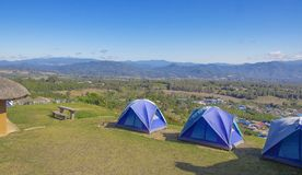 Tre tält av blått på de höga kullarna Himmel och berg för bakgrund blå royaltyfria foton