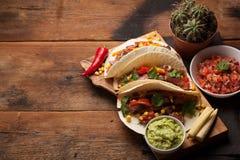 Tre taci messicani con manzo marmorizzato, Angus nero e le verdure sulla vecchia tavola rustica Piatto messicano con il guacamole immagini stock