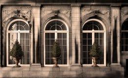 Tre tappningdesignfönster på fasaden av ett gammalt hus, med Arkivbilder