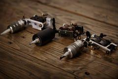 Tre tatueringvapen som är ordnade på en brun trätabell Arkivfoton