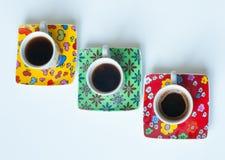 Tre tazze di caffè luminose con caffè espresso caldo su una superficie bianca Fotografie Stock Libere da Diritti