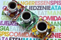 Tre tazze di caffè luminose con caffè espresso caldo su una superficie variopinta Fotografia Stock