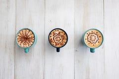 Tre tazze di caffè sistemate simmetricamente e aspettano per dividere immagine stock