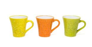 Tre tazze di caffè variopinte isolate su fondo bianco immagine stock
