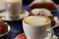 Tre tazze di coffe e dei croissants Immagine Stock