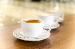 Tre tazze di coffe nella linea diagonale Fotografie Stock