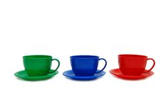 Tre tazze di colore - giocattoli su una priorità bassa bianca Fotografia Stock
