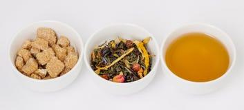 Tre tazze di tè, delle foglie di tè e dello zucchero Immagine Stock Libera da Diritti
