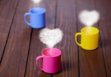 Tre tazze di tè o di caffè con le forme del cuore Immagini Stock