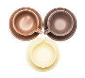 Tre tazze e piattini di caffè fatti di cioccolato Immagini Stock