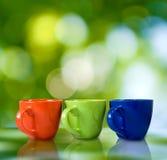 Tre tazze su un fondo verde Fotografia Stock Libera da Diritti