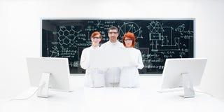 Tre tecnici di laboratorio vestiti nel bianco fotografia stock