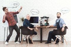 Tre teknikerer arbetar med en skrivare 3d i ett modernt laboratorium De har pratsamma moln över deras huvud Arkivbild
