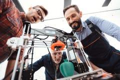 Tre teknikerer glädjas för att se hur skrivaren 3d skrivev ut en äpplemodell Fotografering för Bildbyråer