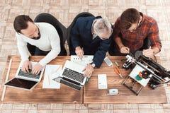 Tre teknikerer sitter på tabellen Arbete två för datorer, medan tredjedelen konfigurerar en skrivare 3d Arkivbild