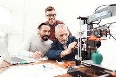 Tre teknikerer skrivar ut detaljerna på skrivaren 3d En äldre man kontrollerar processen Två andra följer processen Royaltyfri Foto