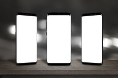 Tre telefoni cellulari con lo schermo per il modello sulla tavola Fotografia Stock Libera da Diritti