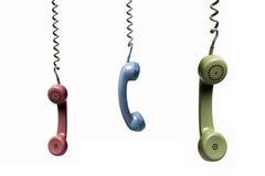 Tre telefoni che pendono da parecchi colori Fotografia Stock Libera da Diritti