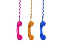 Tre telefoni variopinti che pendono da un cavo Fotografie Stock Libere da Diritti