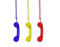 Tre telefoni variopinti che pendono da un cavo Immagini Stock