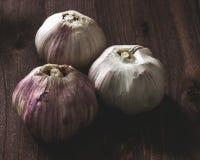 Tre teste di aglio su fondo di legno immagini stock