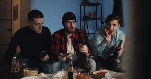 Tre tifosi stanno piantando per la loro squadra di football americano favorita a casa dalla TV Gli uomini bevono la birra e mangi video d archivio