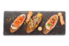 Tre tipi di aperitivi su un bordo isolato Immagini Stock Libere da Diritti