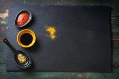 Tre tipi di salse - la salsa al pomodoro, la salsa di soia ed il pesto sauce su una pietra e su un fondo di legno immagine stock