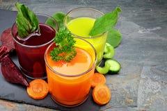Tre tipi di succhi di verdura organici con gli ingredienti sull'ardesia Fotografia Stock