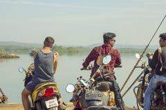 Tre tipi indiani sui motocicli sul traghetto contro lo sfondo del fiume e del verde fotografia stock