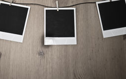 Tre tomma ögonblickliga foto som hänger på klädstreck på träbakgrund, konstbegrepp Fotografering för Bildbyråer