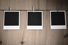 Tre tomma ögonblickliga foto som hänger på klädstreck på träbakgrund, konstbegrepp Arkivbilder