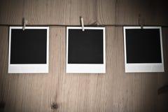Tre tomma ögonblickliga foto som hänger på klädstreck på träbakgrund, konstbegrepp Royaltyfria Bilder