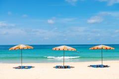 Tre tomma sunbeds och strandslags solskyddparasoller på sand sätter på land royaltyfri foto