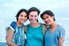 Tre tonår tillsammans och att skratta Multietnisk grupp Arkivbild