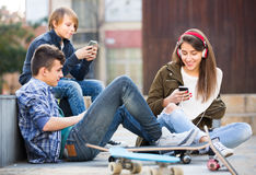 Tre tonåringar med smartphones Fotografering för Bildbyråer