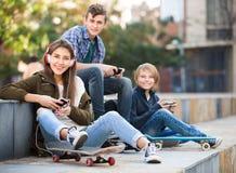 Tre tonåringar med smartphones Arkivfoton